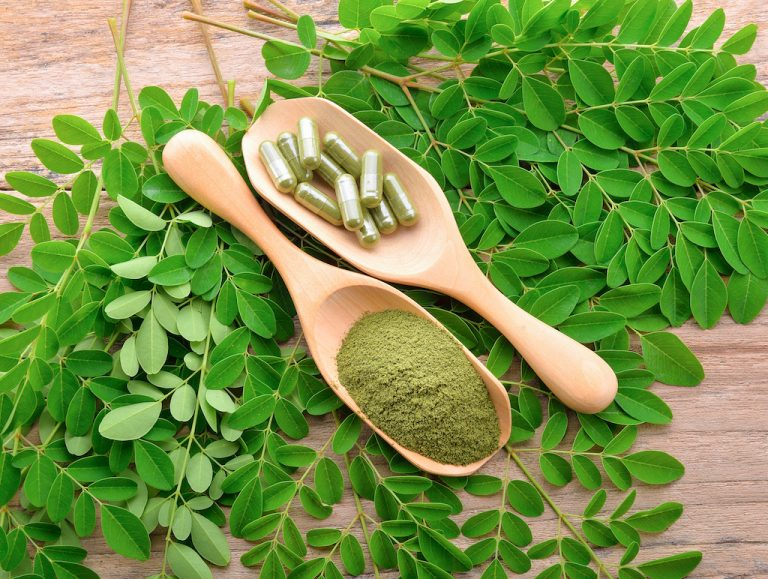 moringa leaf and powder capsule on  a wooden background